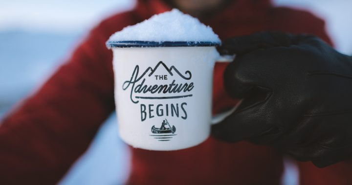 The Adventure Begins mug with snow on it.