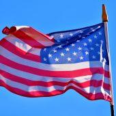 An American Flag flying against a blue sky.