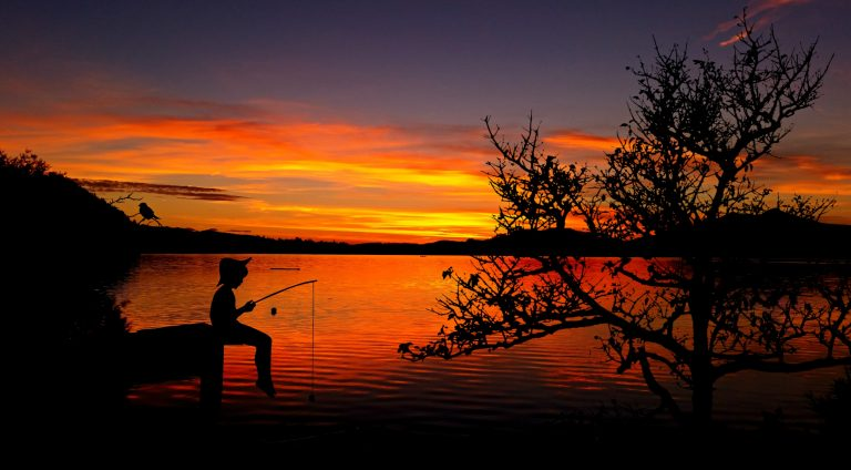 A boy fishing on a pier at a Texas lake at sunset.