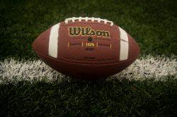 A Wilson football sitting on a football field.
